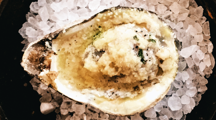 A chilled oyster with seasonings sits on a bed of crushed ice.